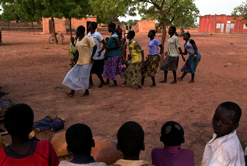 Girls dance to traditional music in the village as other villagers look on at the end of the week. The UNGVT collective purchased traditional musical instruments for collective use in the village.Tanlili, Burkina Faso.Photo © J.B. Russell