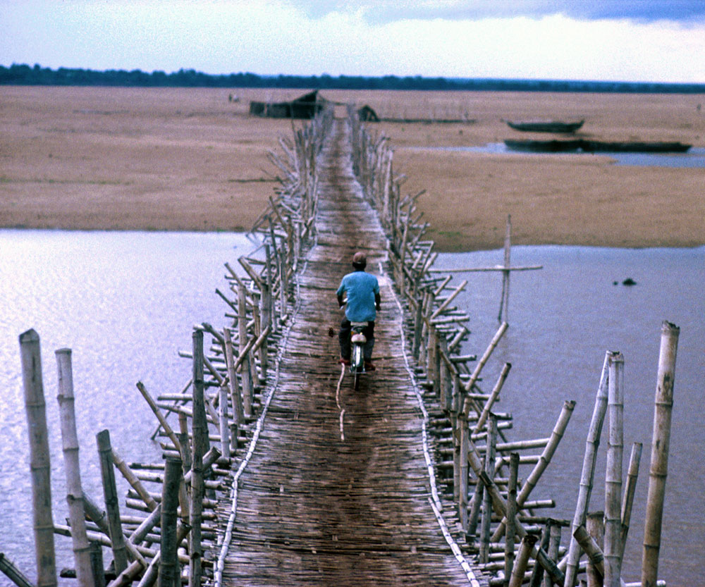 A man crosses the Mekong river on a bicycle during the lead-up to UN organized elections in the war ravaged country.Kompong Cham, Cambodia.Photo © J.B. Russell