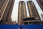 Luxury apartment buildings under construction in the new Pudong financial district of Shanghai. China's booming economy is bringing wealth to many and improving living standards, but soaring demand for energy is having serious effects on the environment. 75% of China's energy needs are supplied by coal, the cheapest and dirtiest form of energy.Shanghai, China.Photo © J.B. Russell