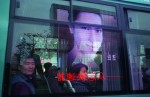 Large screen advertising monitors reflected in a city bus on Nanjing Donglu, Shanghai's shopping street. China's booming economy is bringing wealth to many and improving living standards, but soaring demand for energy is having serious effects on the environment. 75% of China's energy needs are supplied by coal, the cheapest and dirtiest form of energy.Shanghai, China.Photo © J.B. Russell