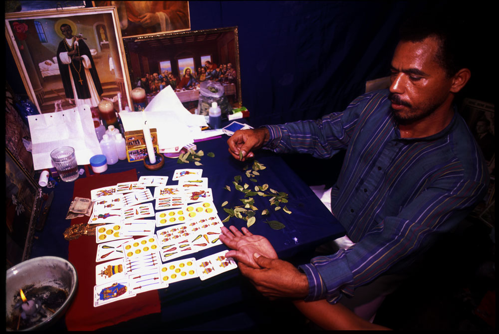 Professor Rafael, a mystic, uses coca leaves to read fortunes. The coca plant and its leaves play an important role in the traditional way of life for indigenous Bolivians. El Chapare, in Bolivia's central lowlands, is the country's principle coca producing region and the heart of the war on drugs.Eterazama, El Chapare, Bolivia.Photo © J.B. Russell