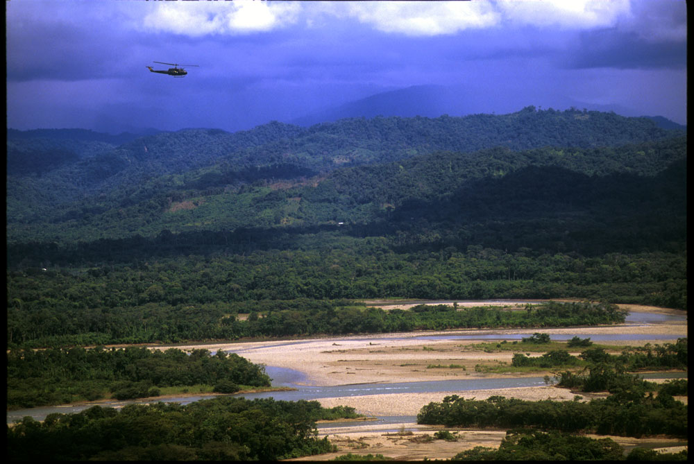 Special narcotics forces (UMOPAR) on an aerial patrol over dense jungle where coca leaves are processed into cocaine paste.  El Chapare, in Bolivia's central lowlands, is the country's principle coca producing region and the heart of the war on drugs.El Chapare, Bolivia.Photo © J.B. Russell
