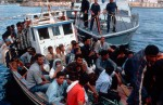 A boat load of illegal immigrants, for the most part Iraqi Kurds and North Africans, is escorted into port by Italian Coast Guard patrol boats. The immigrants depart from Tunisia, sail into Italian waters around it's Mediterranean islands and make an SOS call. According to international maritime regulations, the Italian authorities are obliged to accompany them to the nearest port which is the gateway to the open borders of Europe.Lampadusa, Italy.Photo © J.B. Russell
