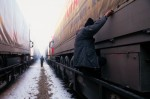 A man climbs out from a hiding place under a freight train along the Austrian-Hungarian frontier. The new eastern members of the European Union, for decades countries of emigration, are now on the front lines of the fight against illegal immigration into the open borders of Europe.Hegyeshalom, Hungary.Photo © J.B. Russell