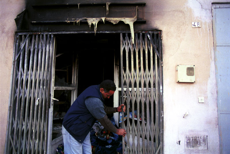 A Moroccan man closing his shop after it was ransacked and burned during violent, racist attacks against the immigrant community. Moroccan immigrants, many of whom enter the country illegally, work as low paid, itinerant laborers in thousands of hothouses across Spain's southern Andalucia region. The region produces vegetables and fruit for export to the rest of the European Union.El Ejido, Spain.Photo © J.B. Russell