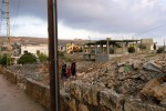 Children cross the ruins of homes destroyed during the 2006 Hezbollah - Israel conflict. The village, near the border with Israel, was severely contaminated with cluster sub-munitions.Yohmour, Lebanon.Photo © J.B. Russell