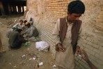 Drug addicts smoke and inject heroin under a bridge along a sewage canal. Many of the addicts are Afghan refugees. Afghanistan is the world's largest poppy producing nation and exports opium and heroin to its neighbors as well as to the rest of the world.Quetta, Pakistan.Photo © J.B. Russell