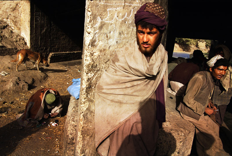 Drug addicts smoke and inject heroin under a bridge along a sewage canal. Many of the addicts are refugees from neighboring Afghanistan. Afghanistan is the world's largest poppy producing nation and exports opium and heroin to its neighbors as well as to the rest of the world.Quetta, Pakistan.Photo © J.B. Russell