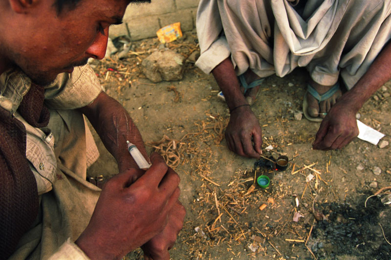 Drug addicts prepare and inject heroin under a bridge along a sewage canal. Many of the addicts are Afghan refugees. Afghanistan is the world's largest poppy producing nation and exports opium and heroin to its neighbors as well as to the rest of the world.Quetta, Pakistan.Photo © J.B. Russell