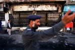 A Pakistani policeman inspects a bank that was destroyed by demonstrators protesting the US bombing of the Taliban regime in Afghanistan. Demonstrators ransacked and burned numerous buildings in the city.Quetta, Pakistan. Photo © J.B. Russell