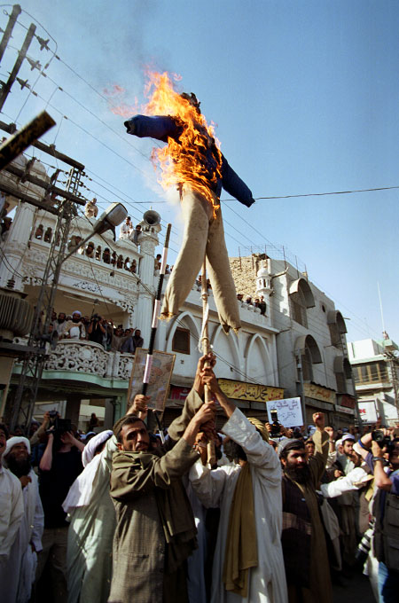 Demonstrators burn an effigy of President George W. Bush after Friday prayers at a mosque in the southwestern city of Quetta. A nation wide general strike and rally was called for by the Jamiat Olema Islami political party and  the Afghan Defense Council, a coalition of religious groups, to protest US threats against the Taliban and the Pakstani government support of the United States.Quetta, Pakistan.Photo © J.B. Russell