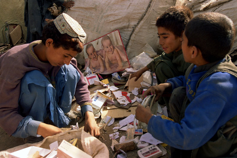 Afghan refugee children collecting paper, plastic and bits of metal to sell at garbage depots for a couple of rupees per kilo. Most long term Afghan refugee families in Pakistan rely on traditional crafts and trading to survive.  Entire families must work, including the children, to get by. The majority of children go to school and work, however the poorest families need their children to work full time depriving them of an education.Quetta, Pakistan. Photo © J.B. Russell