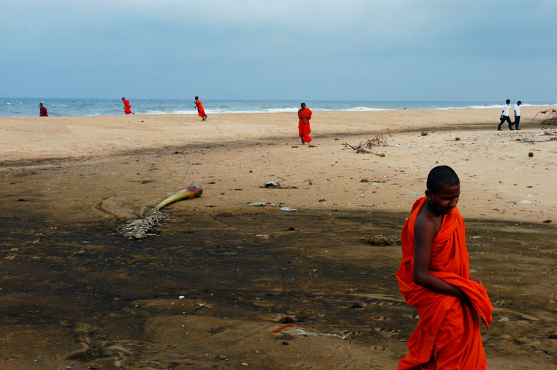 Novice Buddhist monks stroll in contemplation along the beaches of S.E. Sri Lanka, one of the areas hardest hit by the Tsunami on December 26th, 2004.Kalmunai, Ampara District, Sri Lanka.Photo © J.B. Russell