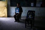 "Zhang Hua Shan, 37, holding a picture of his daughter Zhang Qiu Yue, 12, at Fuxin No.2 Primary  School in Mianzhu, Sichuan province Ma, 2008.  ""The building is dangerous so they moved the older kids to another shool. I want to know why they put the younger children to this builindg."""