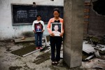 Zhao Xiao Qiong, 36, holding a picture of  daughter Lan Xiao Juan, 10, right, and Yang Zai Yin, holding a picture of  son Liu Chao, 12, at Fuxin No.2 Primary  School in Mianzhu, Sichuan province May, 2008. Both mothers have only one child.