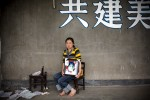 "Yang Zong Chun, 30, holding a picture of her daughter Shi Xue, 10, at Fuxin No.2 Primary  School in Mianzhu, Sichuan province May 24, 2008.   ""I just want people to know about what happened here. """