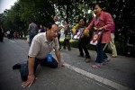 Jiang Guohua, the Communist Party secretary of Mianzhu city, kneels on the ground pleading with protesting parents, whose children were killed in a school collapse during the earthquake, not to complain to higher authorities, Sichuan, China, May 2008. Despite Jiang's pleas, the parents of the 127 children who died in the collapse kept marching and eventually met with higher officials, who told them the government would investigate.