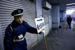 An elderly man works as a security guard, holding a sign of a funeral home January, 2009 in Osaka, Japan. Security guard is one of few jobs that are available to elderly men.