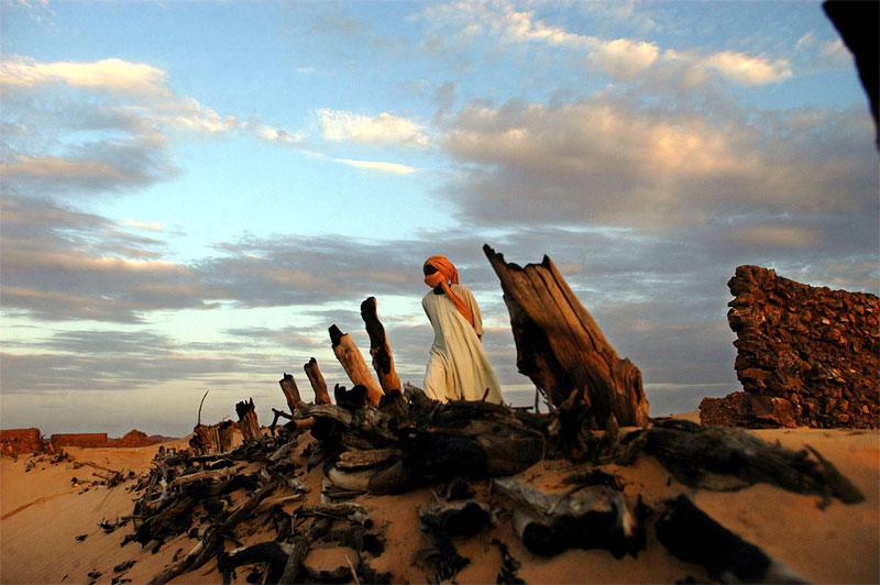 A Sudanese Liberation Army soldier walks through the remains of Hangala village, which was burned by Janjaweed near Farawiya, in Darfur, several months ago, August 27, 2004.  Thousands of ethnic Africans have fled their villages in search of shelter in the mountains or in neighboring Chad because of continuing attacks on civilians.