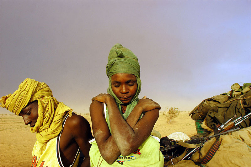 Soldiers with the Sudanese Liberation Army wait by their truck while struck in the mud and hit by a sandstorm in North Darfur, Sudan, August 21, 2004.