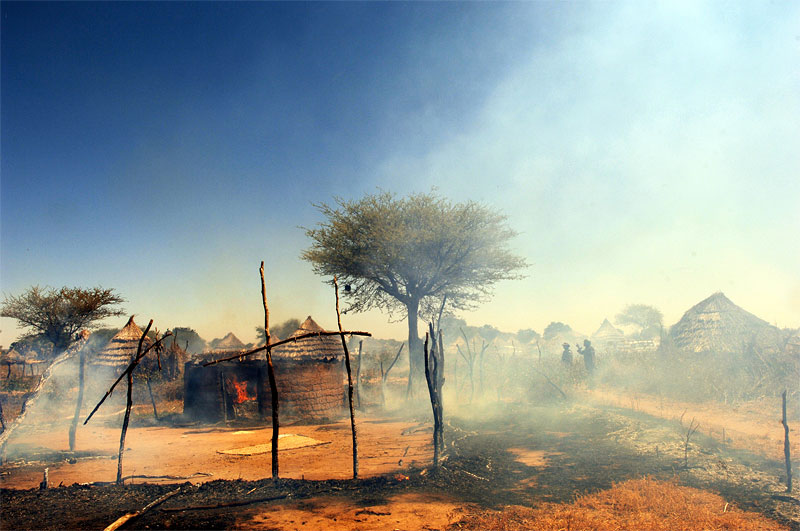 African Union soldiers find the village of Tama freshly burning more than a week after it was originally attacked by Arab Nomads backed by government forces North of Nyala, November 2005.  The AU made several attempts at patrolling and conducting an investigation on the village of Tama after it was attacked, and the surviving villagers fled to a nearby village, and was kept away by nomads who continued to surround the village and shoot at approaching vehicles.  Hundreds of villages have been burned and pillaged throughout Darfur by Arab Nomads, leaving hundreds of thousands of civilians displaced throughout the country.