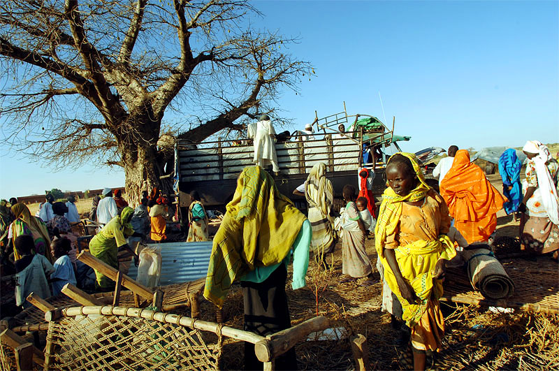 Villagers from Tama carry the remains of their belongings to where they have fled at Uma Kasara village almost two weeks after Tama was attacked, and around 40 people were killed by Arab Nomads backed by government forces North of Nyala, November 2005.  The AU made several attempts at patrolling and conducting an investigation on the village of Tama after it was attacked, and the surviving villagers fled to a nearby village, and was kept away by nomads who continued to surround the village and shoot at approaching vehicles.  Hundreds of villages have been burned and pillaged throughout Darfur by Arab Nomads, leaving hundreds of thousands of civilians displaced throughout the country.