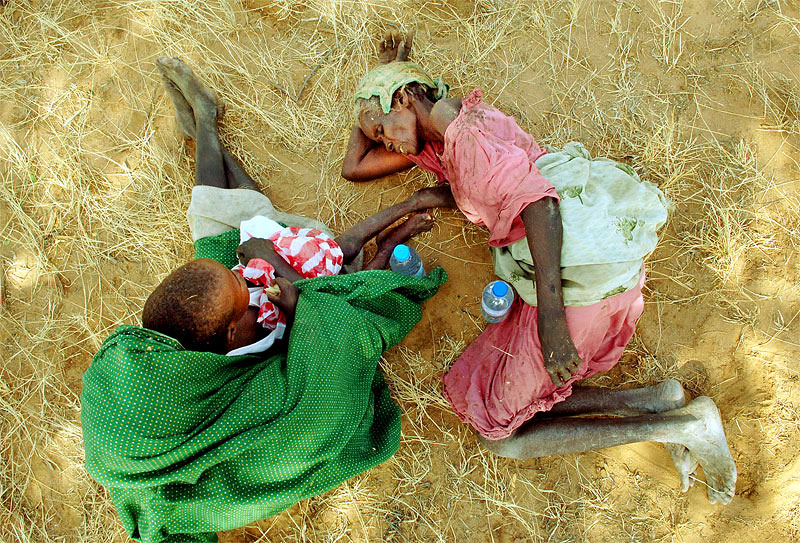 Fatima Abdul Kareem, 65, right, lies beside Kaltoom Nasradeem, 60, shortly after they were picked up by African Union representatives, weak and injured on the side of the road, during an AU investigation of an attack three days prior on Tama village by Janjaweed soldiers in South Darfur, Sudan, October 26th, 2005. More than two years after Darfur's civil war began between Africans and  Arab Janjaweed, backed up by the government, hundreds of thousands of people have been killed, and almost a million have been displaced by ongoing attacks.