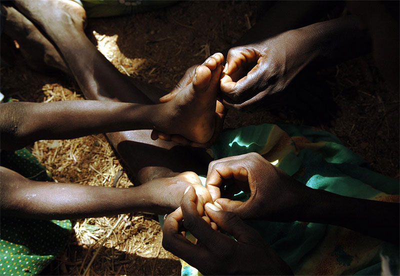 Women from Tama village pick thorns out of the feet of Ibrahim Abakar Ismael, 6, as he lies with his grandmother shortly after being picked up by the African Union three days after he and others fled Tama village as it was being attacked by Janjaweed soldiers in South Darfur, Sudan, October 26th, 2005.  Ismael's parents were both killed in the attack on his village, leaving him with only his grandmother. More than two years after Darfur's civil war began between Africans and  Arab Janjaweed, backed up by the government, hundreds of thousands of people have been killed, and almost a million have been displaced by ongoing attacks.