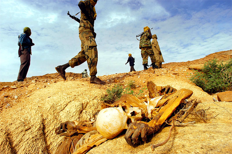 Sudanese Liberation Army soldiers walk past a dead body left from an attack on civilians in the district of Farawyaiah, Darfur, August 24, 2004.  Sixteen bodies lay in the surrounding ravines after men from five nearby  villages were killed allegedly by Janjaweed backed by Sudanese Government forces.