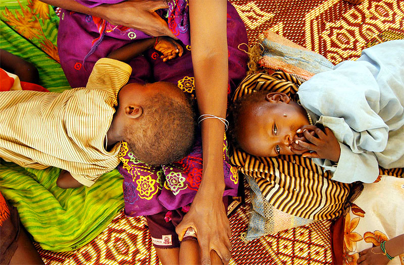 Two malnourished children lie in a feeding center in the Oure Cassone camp in Bahai, Chad, roughly seven kilometers from the Sudan border, August 17, 2004.  Thousands of refugees have streamed out of Sudan into Chad in recent months as fighting persists in Darfur.