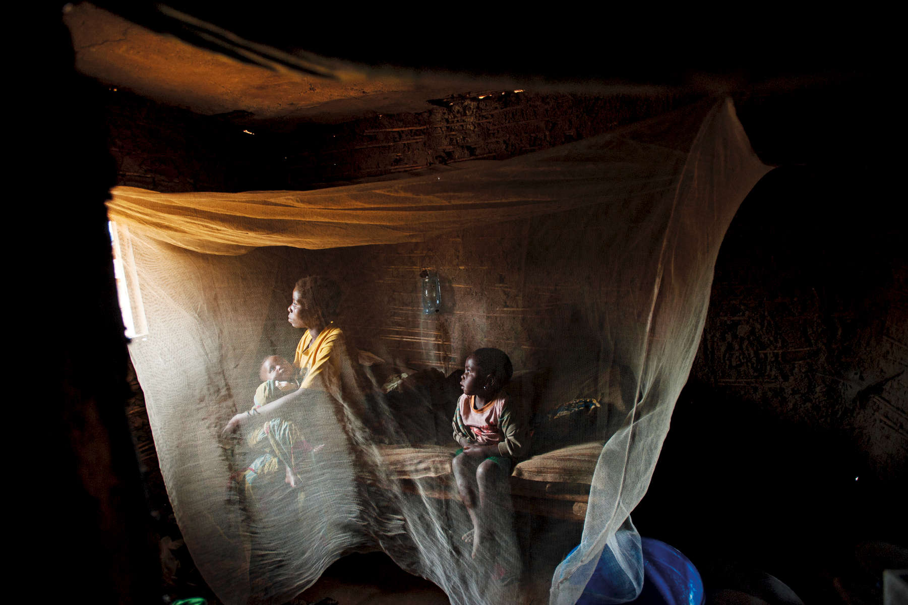 Kahindo, twenty, sits in her home with her two children born out of rape in NorthKivu Province, eastern Congo, April 2008.Prisoners wait