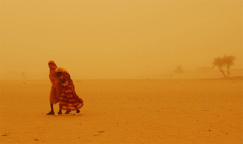 Chadian girls brave a sandstorm in Bahai, Chad, roughly seven kilometers from the Sudan border, August 18, 2004.  Thousands of refugees have streamed out of Sudan into Chad in recent months as fighting persists in Darfur.