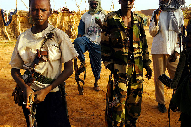 Khalid Saleh Banat, 13, a soldier with the Sudanese Liberation Army, stands with other SLA soldiers after training in the morning in the village of Shigekaro, in Darfur, August 22, 2004.  Khalid has been with the SLA for two years, joining at the minimum age for a soldier at 11.