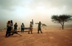 Soldiers with the Sudanese Liberation Army stand around  their weapons during a sandstorm in the village of Shigekaro, in Darfur, August 22, 2004.  The SLA is one of several of the Sudanese rebel groups controlling parts of Darfur in opposition to the Sudanese government.