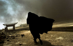 An Iraqi woman walks through a plume of smoke rising from a massive fire at a liquidgas factory as she searches for her husband in Basra, Iraq, May 2003.