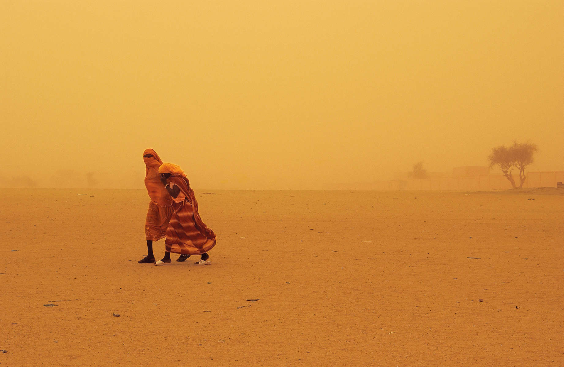 Two women walk though a sandstorm in Bahai, Chad, along the border with Darfur, Sudan, August 2004.