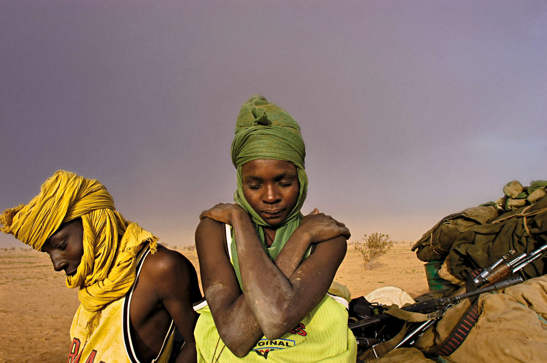 Soldiers with the Sudanese People's Liberation Army sit by their truck, waitingfor it to be repaired, as a sandstorm approaches in Darfur, Sudan, August 2004.