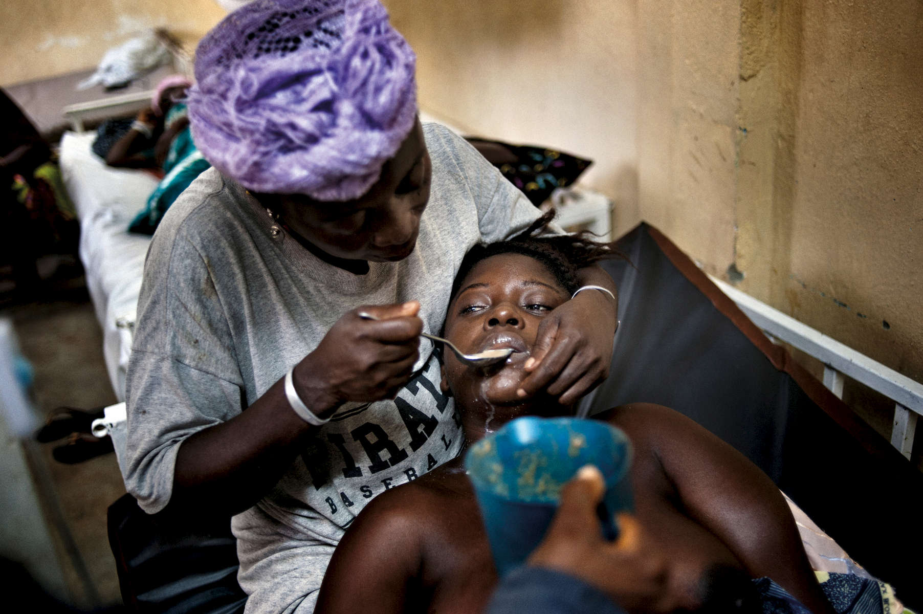 Rukiatu Gbassah feeds her daughter, Adama Gbassah, thirty-one, who remains in a comadue to complications associated with preeclampsia days after delivering her first child atthe Gondama Referral Center in Bo District, Sierra Leone, October 2012