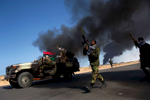 Opposition troops burn tires to use the thick smoke as cover from air strikes at the maincheckpoint near the refinery as rebel troops pull back from Ras Lanuf in eastern Libya,March 2011.