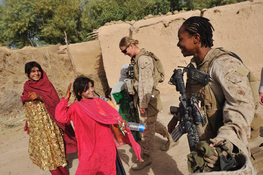 United States Marines, Cpl. Christina Oliver, 25, right, takes off her helmet to show she is a female as a Female Engagement Team is invited by an Afghan girl into their family home in Sistani Village during an operation to clear out Taliban from the area in preparation for parlimentary elections in Southern Marja, Afghanistan, September 15, 2010.  Though the overall mission of the FET teams is to engage Afghan women, the female marines are increasingly exposed to small arms fire and improvised explosive attacks while on their patrols to access villages.