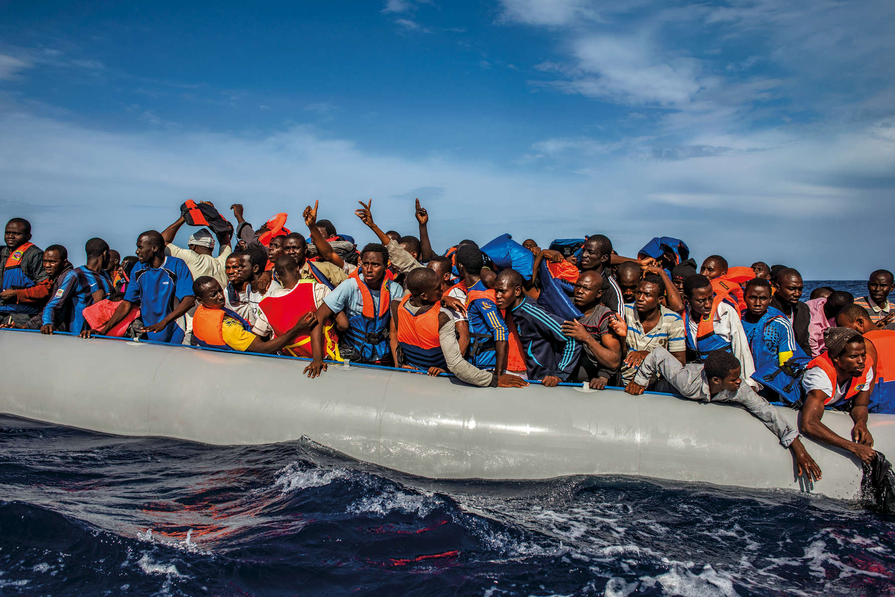One hundred nine African refugees from Gambia, Mali, Senegal, Ivory Coast, Guinea,and Nigeria are rescued by the Italian navy from a rubber boat in the sea between Italyand Libya, October 2014.