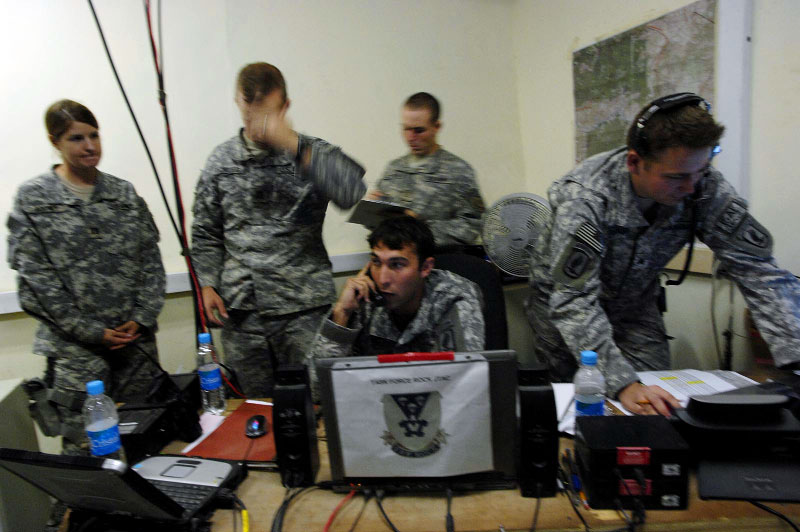 soldiers with the 173rd division, battle company: JTAC Gabe Beck, center, speaks with pilots of bomber jets in the Tactical operations center for Battle company as two different 'troops in contact' incidents unfold on screens in the command center. Beck, a JTAC, is an Airforce-trained specialist in direct contact with the bomber pilots to call in airstrikes on certain targets while weighing and monitoring collateral damage potential. The TOC at camp blessing helps control close air support based on intelligence and input for troops at more forward operating bases, and decisions made by more senior commanders than those on the ground. Left center is captain Jeff Pickler. September 2007.