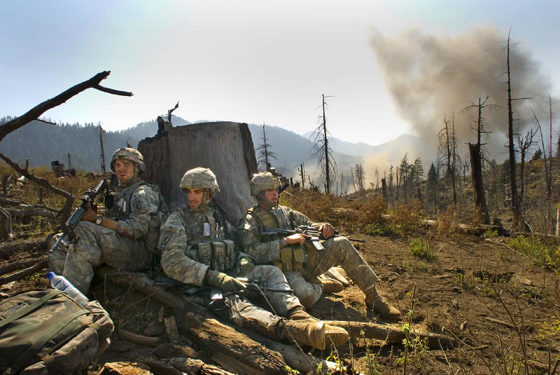 Soldiers stand guard behind a tree stump as they wait for a medevac to come and take away the body of one of their soldiers shortly after the troops were ambushed by the Taliban, Korengal Valley. October 23, 2007.