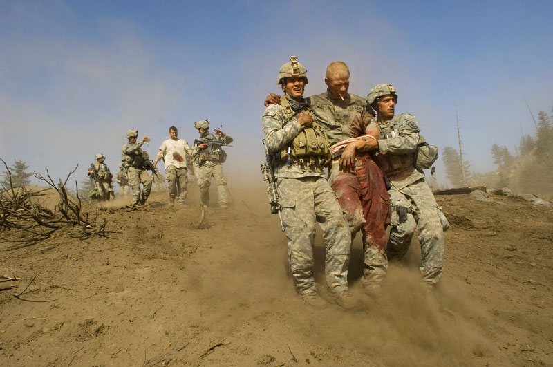 Specialist Carl Vandeberge, center, and Sargeant Kevin Rice, behind, are assisted as they walk to a medevac helicopter minutes after they were both shot in the stomach during a Taliban ambush, which killed one soldier, and wounded both of them.   Spc. Carl Vandeberge and Sgt. Kevin Rice, were flown out immediately for surgery. October 23, 2007.