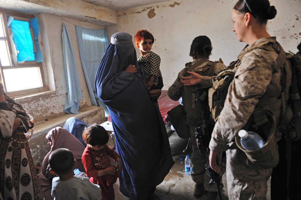 United States Marines with the Female Engagement Teams, Lance Corporal April Whitham, 27, and LC Elisabeth Reyes, 20, visit with Afghan women and their children at the clinic in Now Zad, in Northern Helmand, May 8, 2010. The Female Engagement teams recently helped cordon off part of the clinic to enable Afghan women and men separate sitting areas.