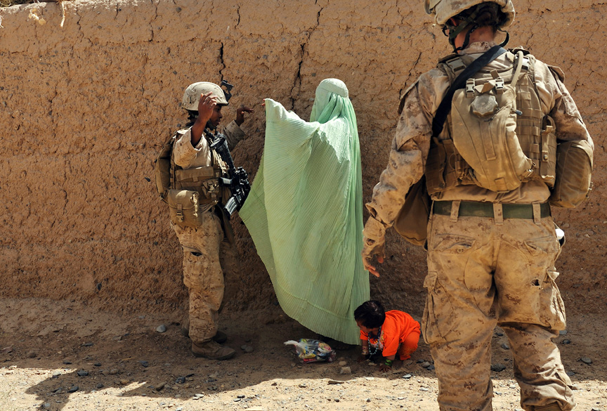 United States Marine, Cpl. Christina Oliver, 25, left, and Lance Cpl. Stephanie Robertson, right, members of the Female Engagement Teams attached to Second Batallian, 6th Marine Regiment, search an Afghan women at a check-point during an operation through Sistani Village to clear out Taliban from the area in preparation for parlimentary elections in Southern Marja, Afghanistan, September 15, 2010.  Though the overall mission of the FET teams is to engage Afghan women, the female marines are increasingly exposed to small arms fire and improvised explosive attacks while on their patrols to access villages.