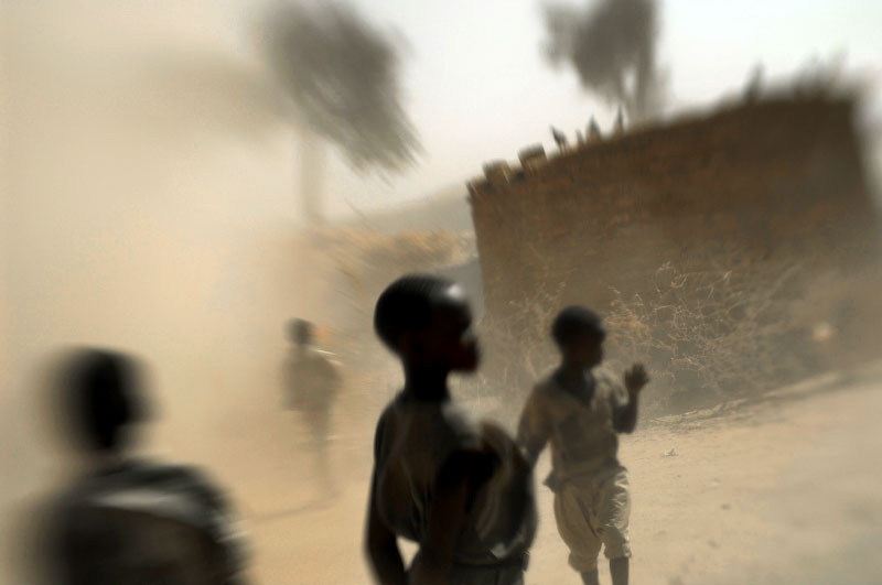 nternally displaced children walk through a sandstorm at Hamadiya camp in Zallingi, in West darfur, February 2007.  Since the beginning of the war in Darfur, over two million people have been displaced from their villages throughout the region, and hundreds of thousands have been killed.