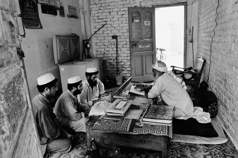 Pakistani and Afghan young men read the Koran at the Jammiah Ashrafiah Madrassa in Peshowar, in the North West Frontier Province of Pakistan, July 5, 2008.  While Madrassas have traditionally been a place for young men to study the Koran in step with Islamic studies, it has also been a breeding ground for young men's hatred towards the West, and a place from which many initiate their Jihadist beliefs. Since the start of the American-led war in Afghanistan in 2001, the Taliban has gradually infiltrated the areas surrounding Peshowar, making the tribal areas inaccessible, and Peshowar more tense.