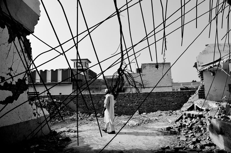 A Pakistani man walks through the destruction left at a police station bombed by the Taliban in June 2008, in one of 10 taliban attacks and suicide bombers in the last six months in the city of Mardan on CD shops, police stations and cinemas, in Pakistan, July 5, 2008.  Since the start of the American-led war in Afghanistan in 2001, the Taliban has gradually infiltrated the areas surrounding Peshowar, trying to force Pakistanis to live by Sharia Law, Islamic Law--to give up music, cinema--especially with images of women without hijab, or the traditional head cover and dress, and entertainment.  In the past years, women in the NWFP have taken on ever more concealing chadors, or full covering of face and body, and more are wearing the Afghan-style burqua. In recent years, the Taliban has been bombing police stations in an attempt to undermine the Pakistani government.
