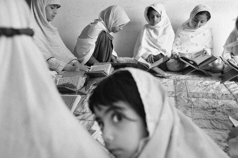 Young girls study the Koran in a private home in Saidu Sharif City, next to Mingora in Swat, in the heart of the tribal area in Pakistan, July 2008.   Since 1995, the Taliban and other religious groups have been trying to bring Mingora under Sharia law, or Islamic Law, rather than the traditional tribal law carried out in the Pakistani tribal areas, and locals are under increased pressure to abide by very conservative branch of islam.  While the tribal area was once a safe, beautiful area of Pakistan, there are now bombings carried out by the Taliban against various locations, including police stations and hotels, and local families fear to even let their children out of the house.